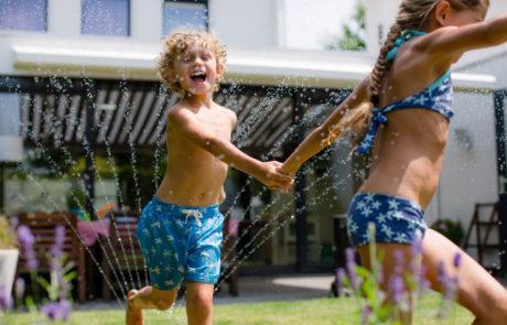 Kinderen rennen door het water van een sproeier
